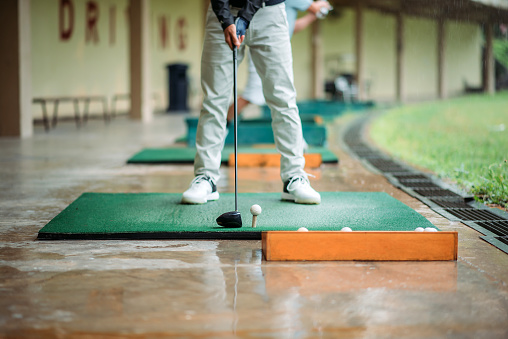 Close up of asian chinese senior man golfer getting ready tee off before swing his golf club at golf driving range