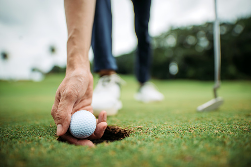 Close up of asian chinese young male golfer picking up golf ball with hand at the hole of golf course