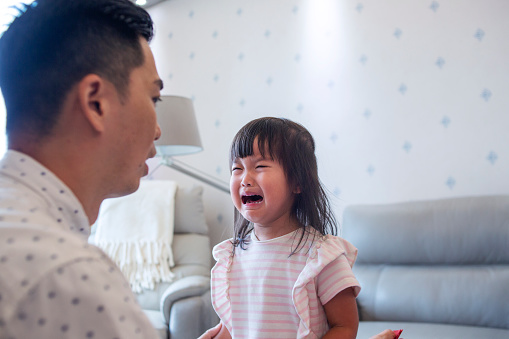 Close up of Asian father consoling cure crying daughter in living room of the house. concept of parenthood