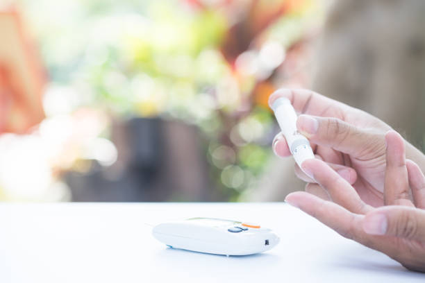 Close up of asian man's  hands using lancet on finger to check blood sugar level by glucose meter, Healthcare medical and check up, diabetes, glycemia, and people concept stock photo