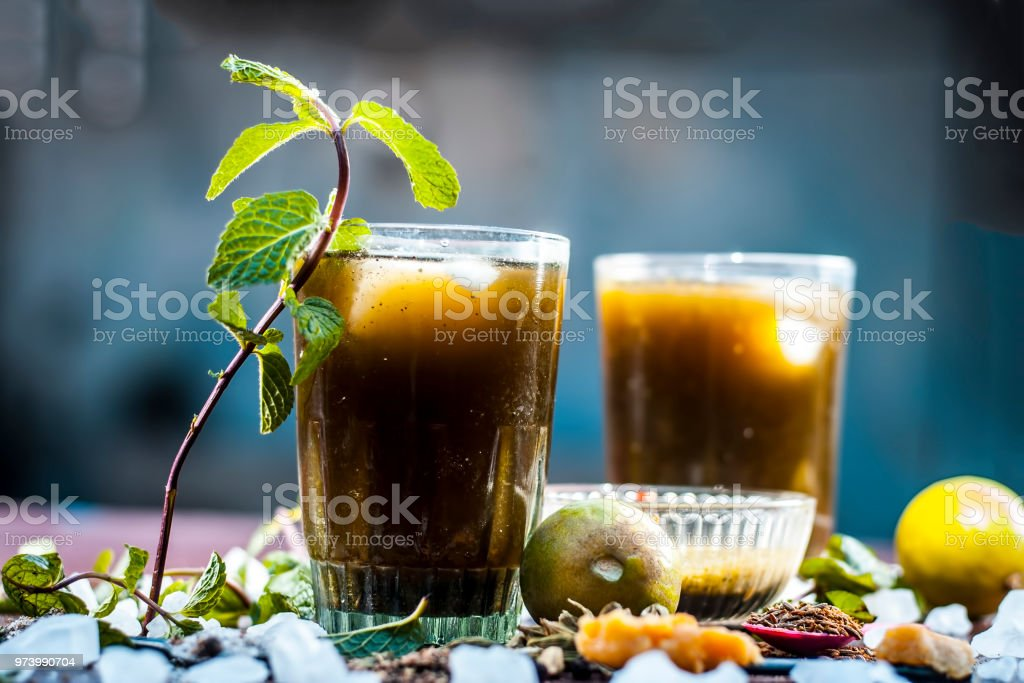 Close up of Asian popular summer drink i.e. Phudina ka shrbat or mint drink with all  its ingredients on a wooden surface which are sugar,mint leaves with its extract,lemon,jaggery and black salt. Close up of Asian popular summer drink i.e. Phudina ka shrbat or mint drink with all  its ingredients on a wooden surface which are sugar,mint leaves with its extract,lemon,jaggery and black salt. Above Stock Photo