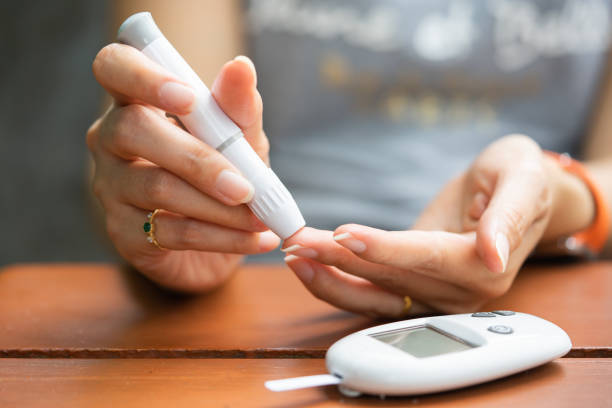 Close up of asian woman hands using lancet on finger to check blood sugar level by Glucose meter, Healthcare Medical and Check up, Medicine, diabetes, glycemia, health care and people concept stock photo