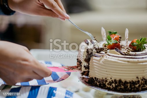 Close up of asian woman slicing a birthday cake