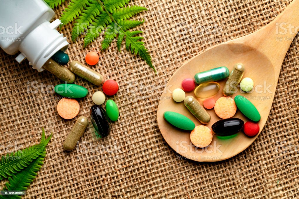 Close up of assorted capsules and pills into wooden spoon on a rustic background stock photo