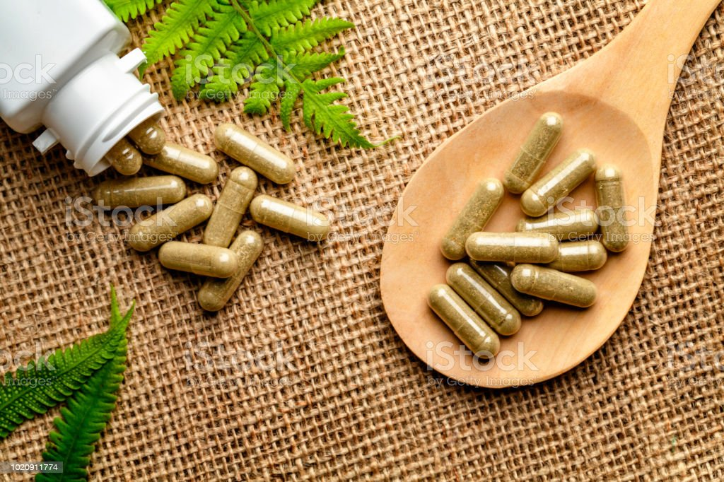Close up of assorted capsules of alternative medicine into wooden spoon on a rustic background stock photo