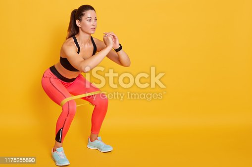 istock Close up of athletic woman in squat in gym, fit girl exercising with resistance band for lower body relief, sporty lady wearing sport clothes and sneakers posing isolated over yellow studio background 1175255890