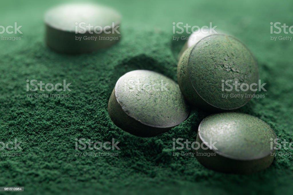 Nahaufnahme der Atisanal Spirulina Tabletten und Pulver – Foto