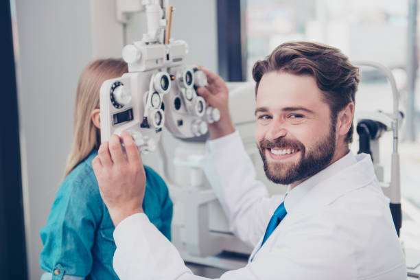 Close up of attractive cheerful brunet bearded optician, doing the eye sight check up for small blond girl at his office, smiling stock photo