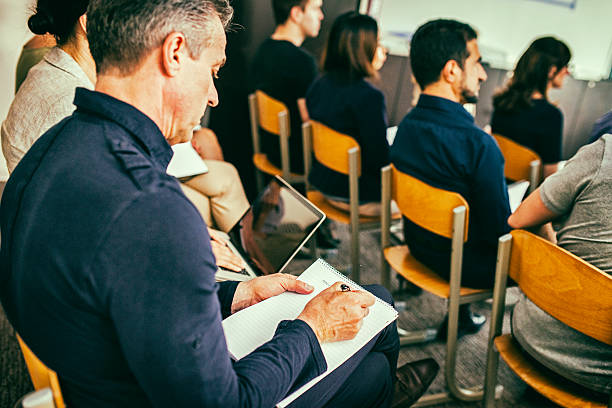 Close up of audience Close up shot of audience in casual clothing listening at seminar. labor union stock pictures, royalty-free photos & images