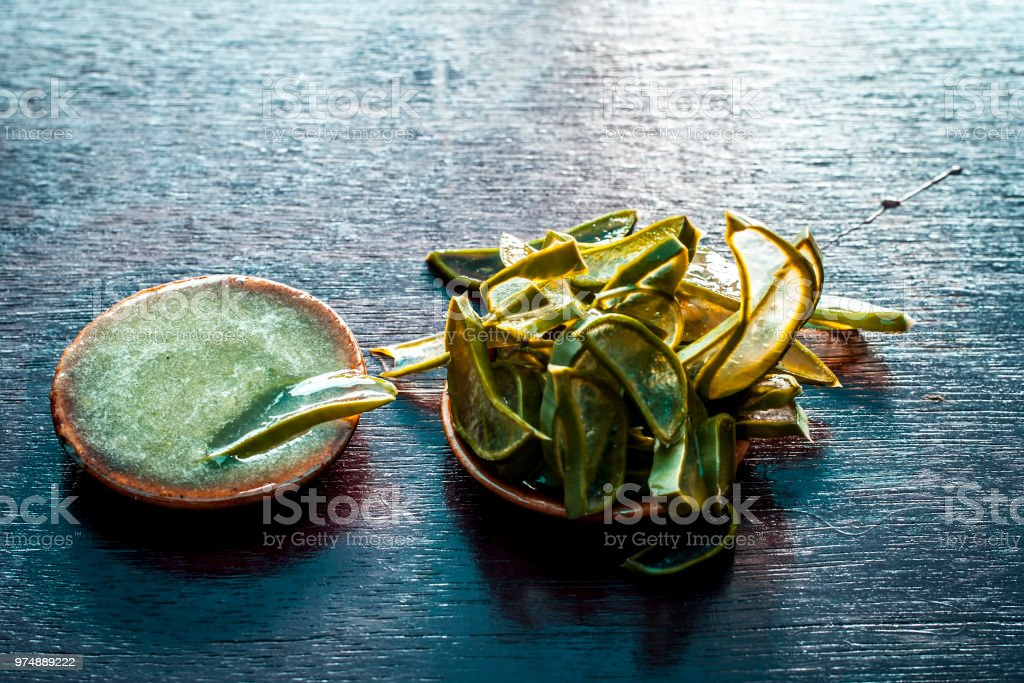 Close up of ayurvedic face pack for removing black skin and acne with its ingredients i.e. Cucumber sliced and Aloe Vera with its gel on a brownish surface in dark Gothic colors. stock photo