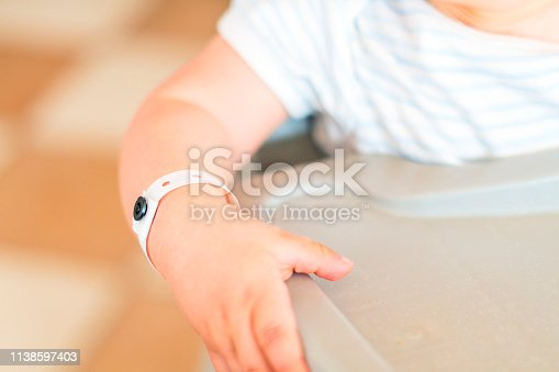 istock Close up of baby boy hand with all inclusive badge 1138597403