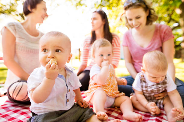 Close up of baby boy in public park, mothers with babies in the background. stock photo