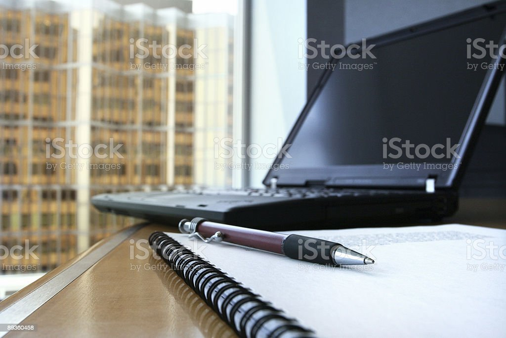 Close up of ball pen on notebook with laptop in background royalty free stockfoto