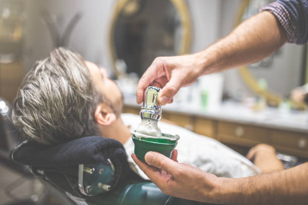 Close up of barber hands preparing foam by using shaving brush and bowl. Client in armchair in the background. Hands of barber with brush for shaving beard and bowl. barber shop shaving brush shaving cream razor old fashioned stock pictures, royalty-free photos & images