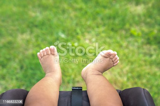 istock A close up of bare skin chubby legs, feet and toes of a mixed race baby boy infant hanging off into the fresh air over the grass at a park as he sits in his car seat stroller in the summer. 1166833206