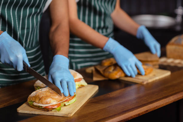 Close up of baristas preparing sandwiches Close up of baristas preparing sandwiches in the bar female sandwich stock pictures, royalty-free photos & images