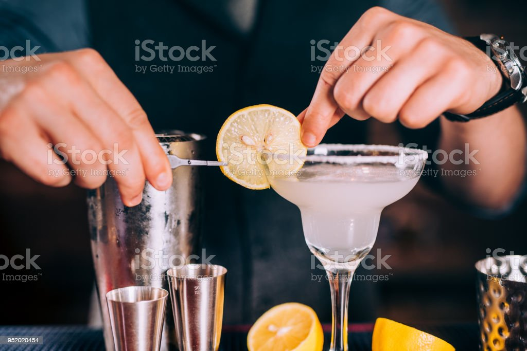 Close up of barman hands preparing margarita cocktail in fancy glass at nightclub stock photo