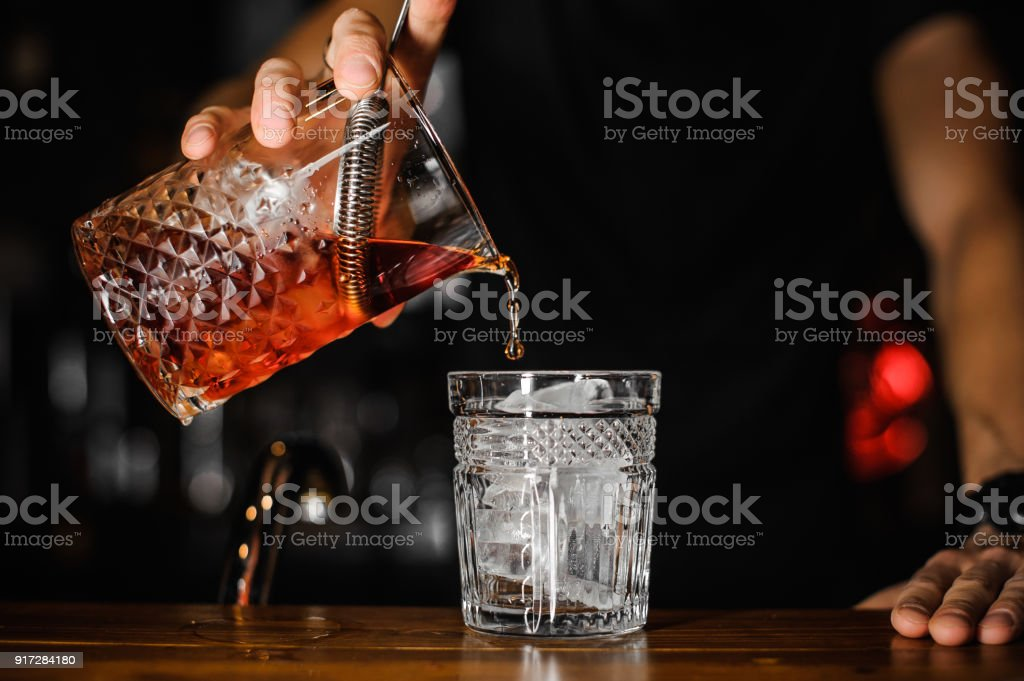 close up of bartender pouring bright red alcohol cocktail into the glass stock photo