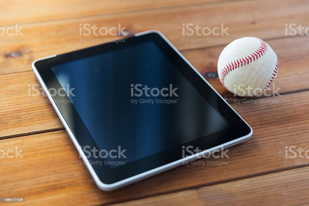 close up of baseball ball and tablet pc on wood stock photo