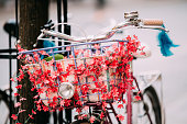 Close Up Of Basket And Hadlebar Of Female Bicycle Equipped Basket With Decorative Flowers Parked In City Street