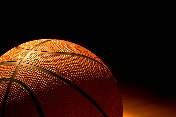 Close up of basketball in low light Close-up of a basketball left on the court all star stock pictures, royalty-free photos & images