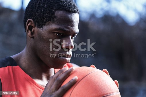 African basketball player in red sport uniform holding a basket ball outdoor. Focus on foreground.