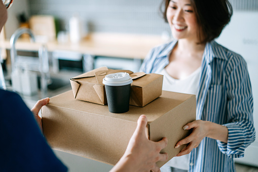Close up of beautiful and cheerful young Asian woman receiving home delivery takeaway food order from a delivery man at home. Eating at home concept