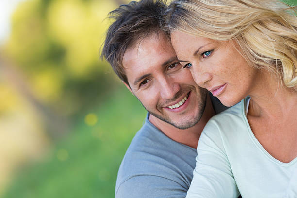 Close up of beautiful couple sitting in the nature Close up of beautiful couple sitting in the nature, selective focus age contrast stock pictures, royalty-free photos & images