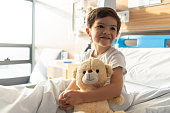 Close up of beautiful little boy hugging his teddy bear while looking away daydreaming and smiling