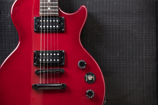 A close up studio shot of a red guitar leaning against an amplifier speaker.