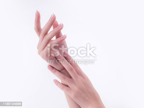 1151624350istockphoto Close up of beautiful Woman Hands. Spa and Manicure concept. Female hands with french manicure. Soft skin, skincare concept. Beauty nails. over beige background 1169134688