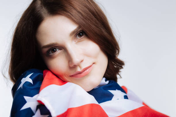 Close up of beautiful woman leaning cheek on US flag stock photo
