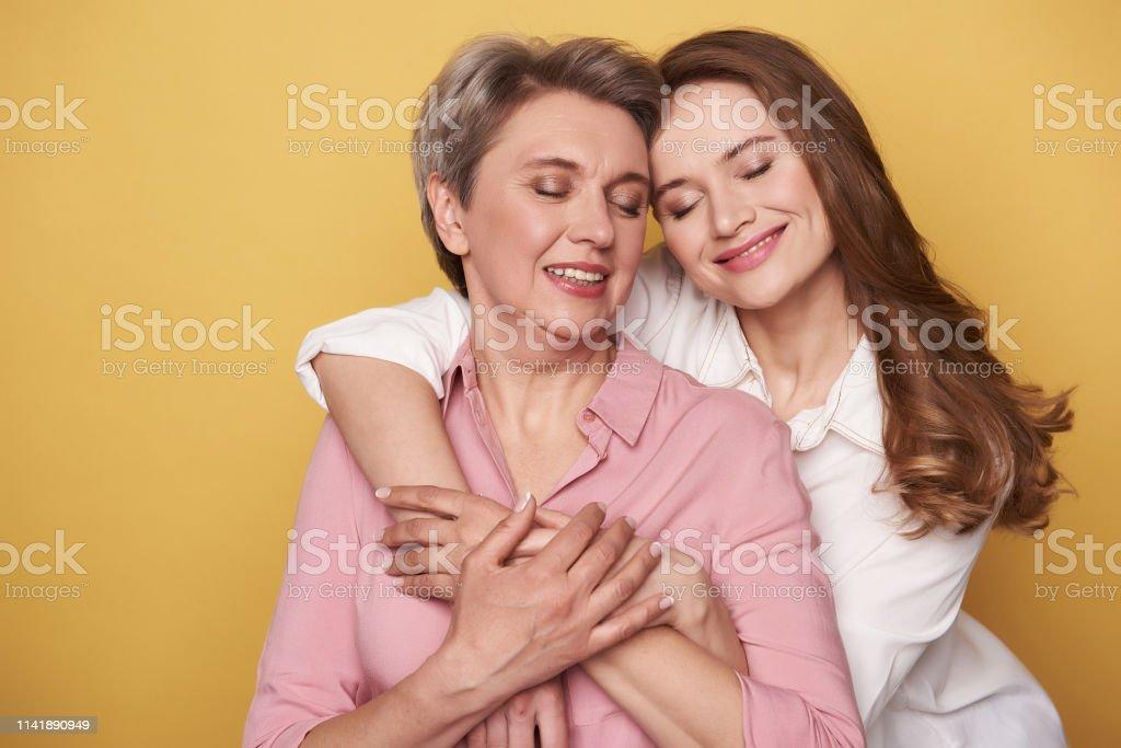 Fermez-vous vers le haut de la belle femme avec sa fille charmante posant pour l'appareil-photo photo libre de droits