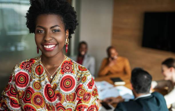 fermer vers le haut de la belle jeune femme d'affaires noire noire de sourire, les collègues tiennent une réunion en arrière-plan - coiffure africaine photos et images de collection