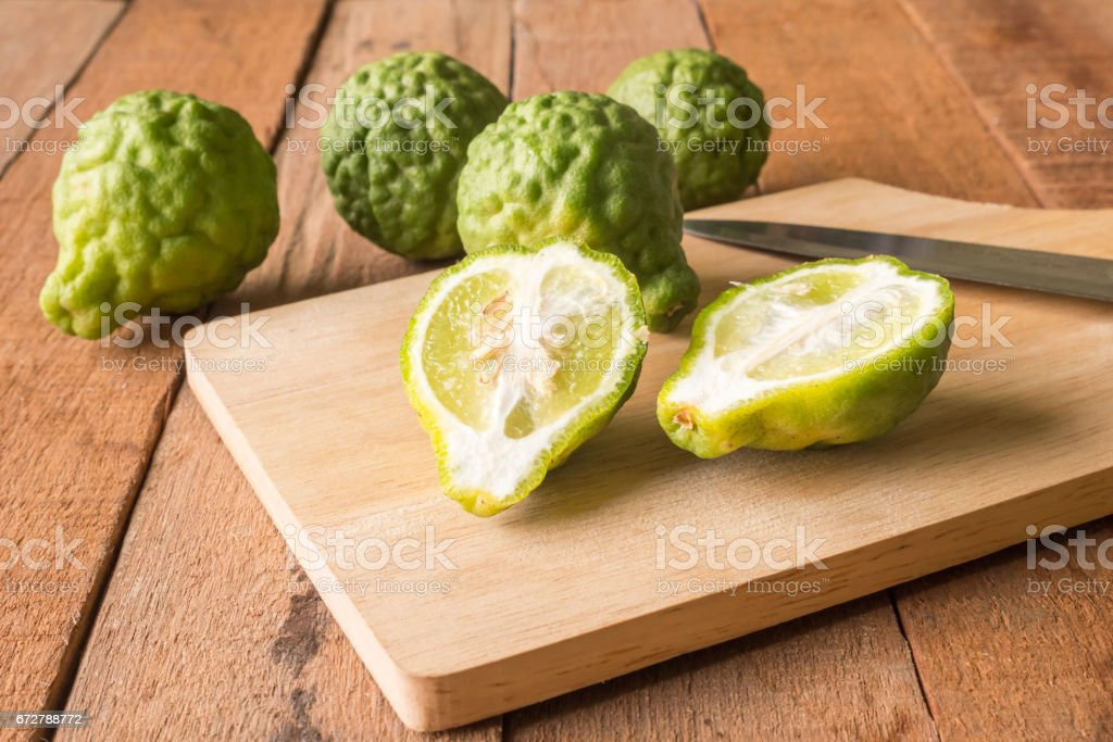 Close up of bergamot or kaffir lime on wooden table background. stock photo