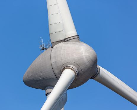 Close up of big wind turbine against a blue sky
