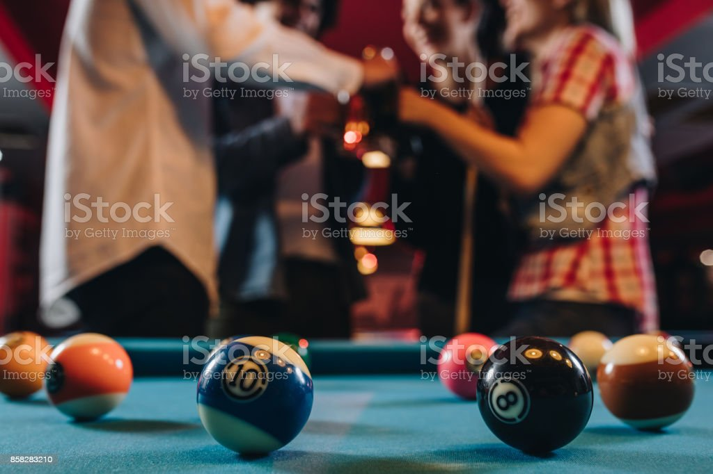 Close up of billiard balls on the table with people in the background. stock photo
