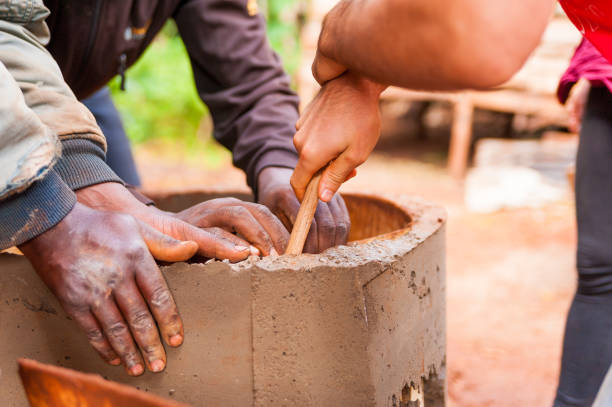close up of black and white hands cooperating to build cement water well in africa village stock photo