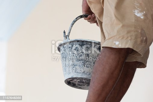 istock Close up of black paint bucket and painter legs. Architecture and Civil engineering concept. Structure and construction. Occupation and job 1152646355