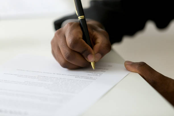 Close up of black worker signing legal documentation Close up of African American worker signing job contract, person being employed at new position, male client putting signature at document in office. Recruiting, promotion, legal documentation concept signing stock pictures, royalty-free photos & images