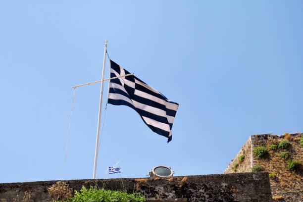 Feche acima da bandeira grega azul e branca no vôo do mastro no vento. Bandeira nacional grega rasgada na construção velha que acena de encontro ao céu azul limpo e às nuvens no fundo. Conceito nacional do Marco. - foto de acervo