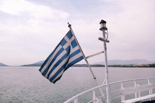 Feche acima da bandeira grega azul e branca no vôo do mastro no vento. Bandeira nacional grega rasgada que acena na curva do navio de encontro ao mar Mediterrâneo azul, céu, nuvens no fundo. Conceito nacional do Marco. - foto de acervo