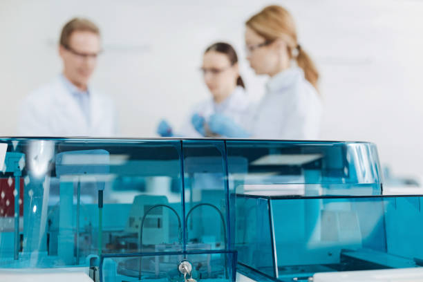 Close up of blue cover while being closed Plastic detail. Three medical workers standing on the background and wearing protective glasses while discussing new experiment dna purification stock pictures, royalty-free photos & images