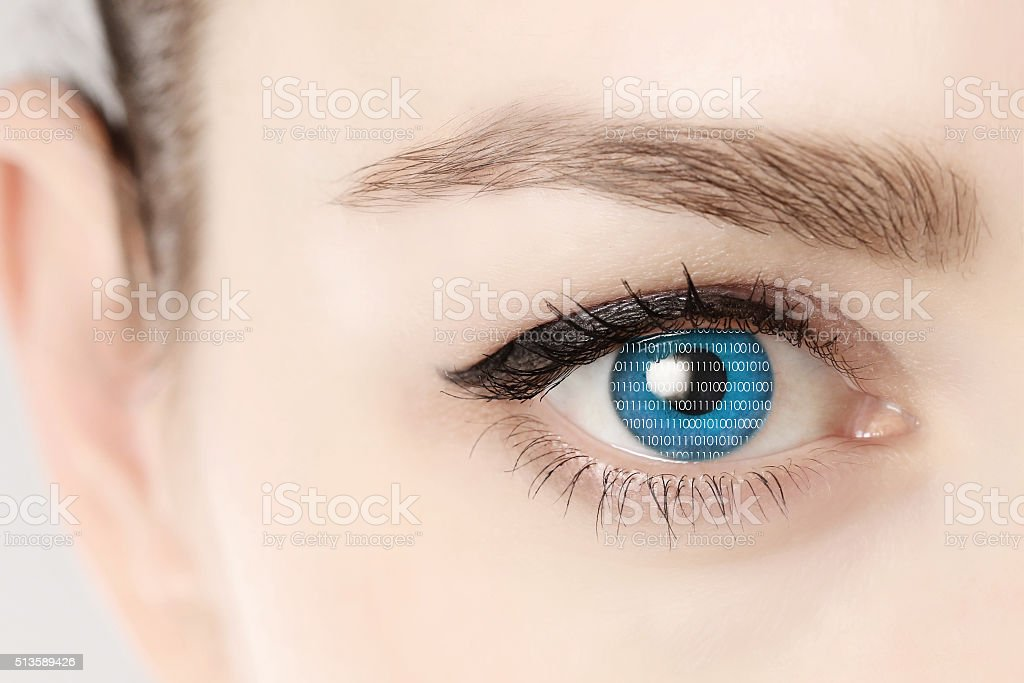 Close up of blue eye of woman showing binary codes stock photo
