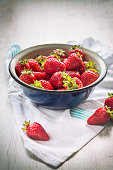 Close up of a blue metal bowl full of fresh strawberries over a white wood rustic background.