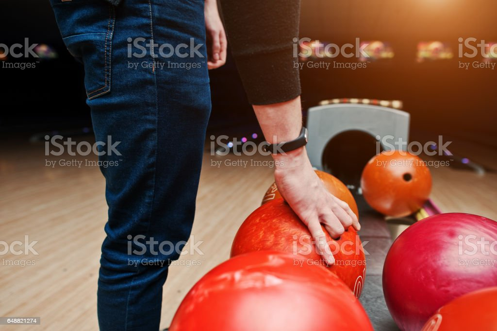 Close up of bowling player hand taking red ball from bowl lift - foto stock