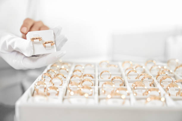Close up of box with wedding rings collection in store Close up of woman hands in white gloves showing collection of wedding rings at jewelry store. Female worker doing professional consulting for demanding clients. Customer service concept jeweller stock pictures, royalty-free photos & images