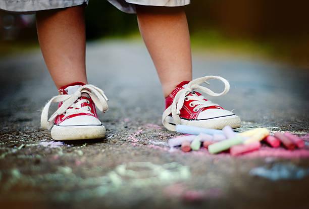 nahaufnahme des jungen zieht mit chalks - malerei schuhe stock-fotos und bilder