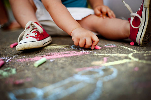 close up of boy drawing with chalks - chalk drawing stock photos and pictures
