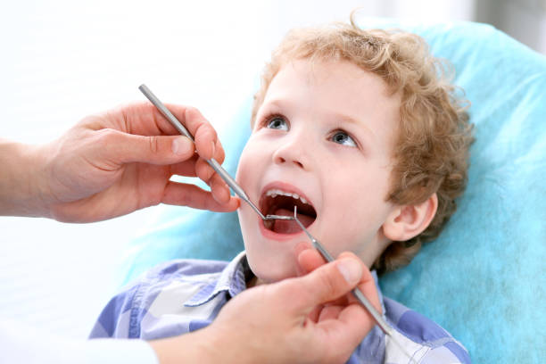 Close up of boy having his teeth examined by a dentist stock photo